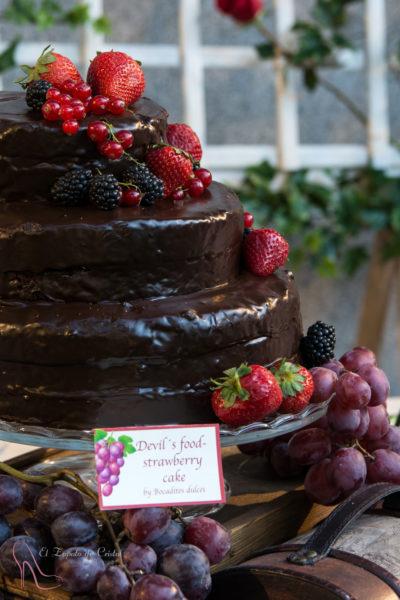 Tarta de tres pisos, forrada de ganache de chocolate y decoarada con frutos rojos.