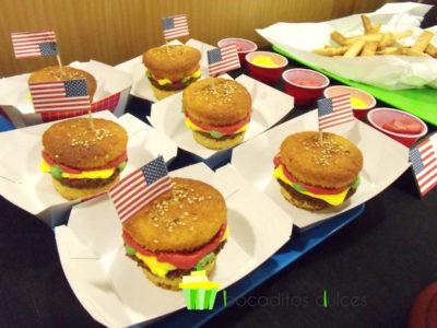 Cupcakes partidos por la mitad y decorados con buttercream de vainilla de color rojo, amarillo y verde simulando lechuga. tomate y queso con una banderita americana pinchada en el bizcocho.