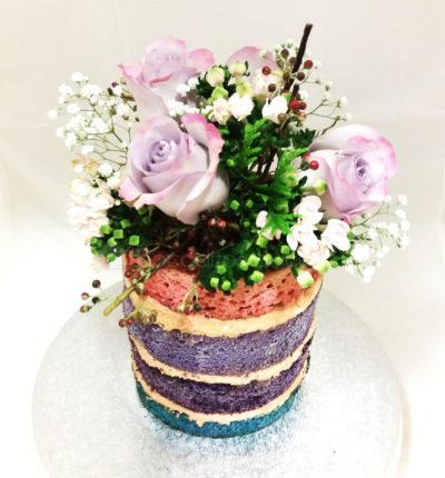 Tarta desnuda, con el bizchoco de diferentes colores, relleno de buttercream de vainilla y decorada con flores naturales.