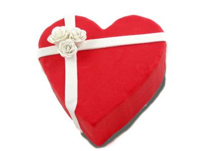 Tarta en forma de corazon forrada con fondant de color rojo, y dos tiras de fondant blanco decoradas con tres rosas blancas de fondant