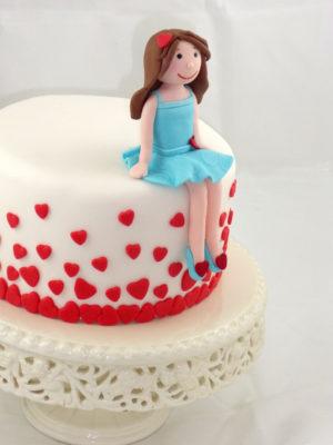 Tarta cubierta de fondant blanco con pequeños corzones de color rojo y una muñeca de fondant sentada sobre la tarta
