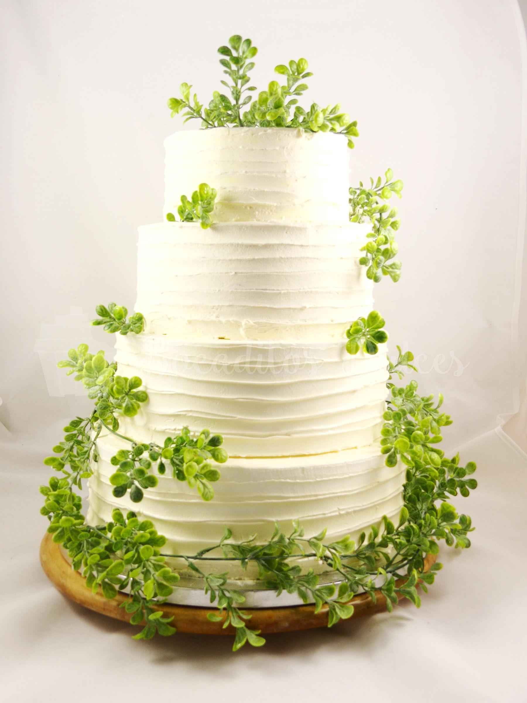 Tarta de cuatro pisos, cubierta de buttercream de color blanco, decorada con hojas .