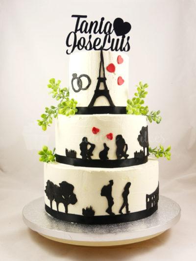 Tarta de tres pisos, cubierta de buttercream blanca, con pequeñas figuras alrededor de la tarta en negro y decorada con hojas y un letrero con el nombre de los novios