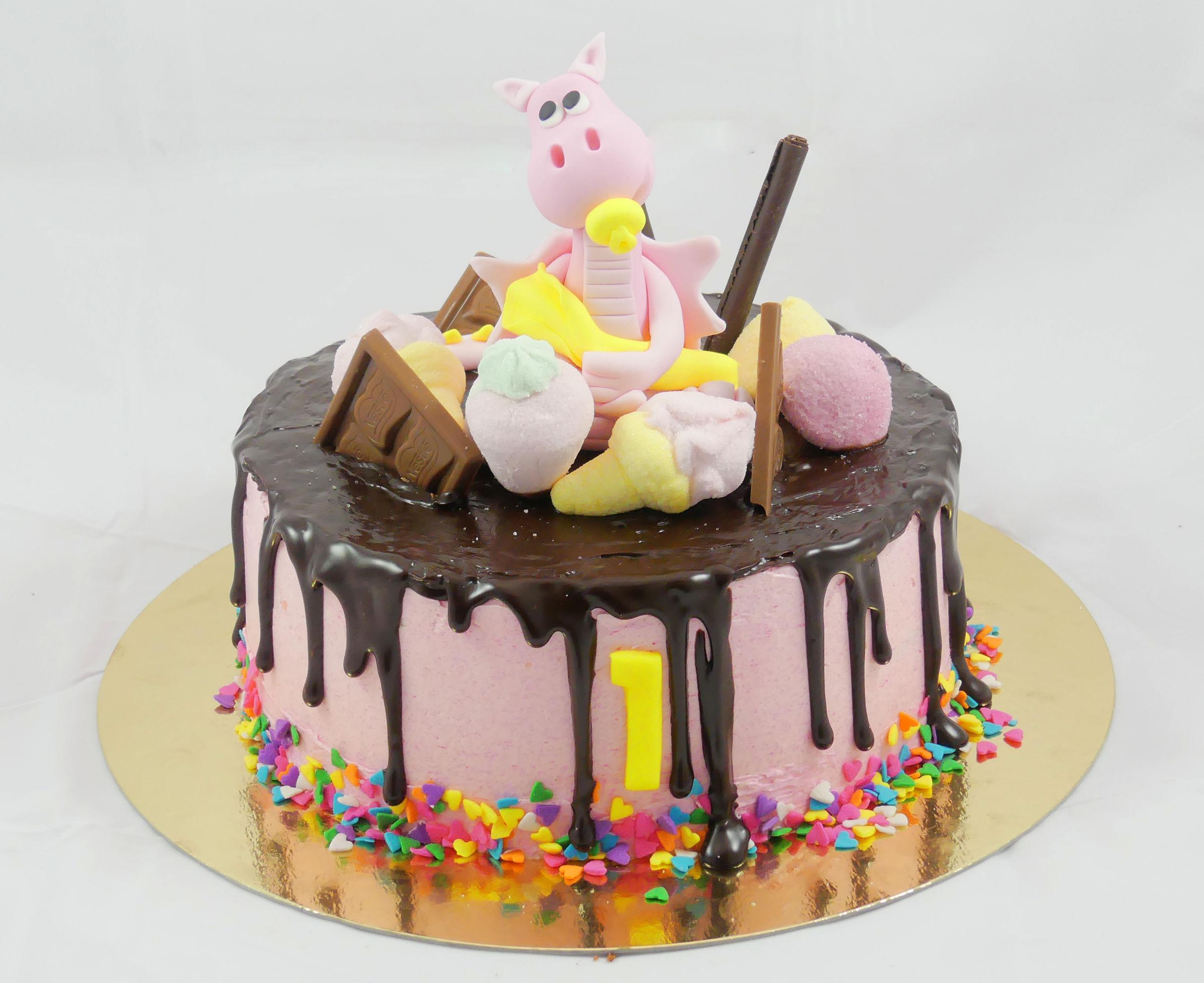 Tarta cubierta con buttercream de color rosa, pequeñas virutas de caramelo alrededor el numero uno en color amarillo, ganache de chocolate por encima y cayendo por los lados diferentes tipos de chocolates y gominolas sobre la tarta junto con un pequeño dragon de fondant