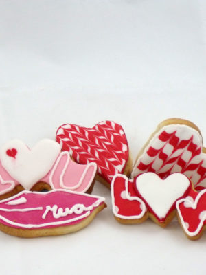 Galletas de mantequilla con forma de corazon decoradas con glasa real de color rojo y blanco, galletas con distintas frases decoradas con glasa real, de color rosa y rojo y galleta con forma de labio decorada con glasa real de color rosa fuerte.