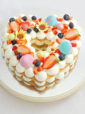 tarta con forma de corazón, base de galleta, crema de queso y decoración de frutas, chuches y chocolates.