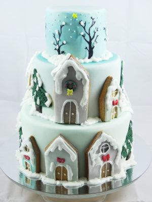 tarta de fondant con decoración pintada con aerógrafo, árboles nevados y casitas de galleta