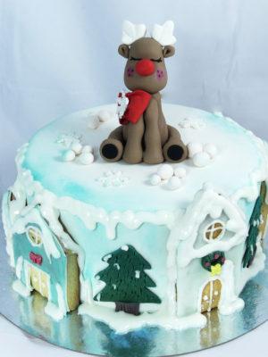 tarta cubierta con fondant y decorada con aerógrafo, abetos nevados, casitas de galleta y una figura de un reno navideño.