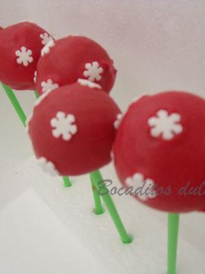 cake pops sencillos navideños con fondo rojo y copos blancos como decoración