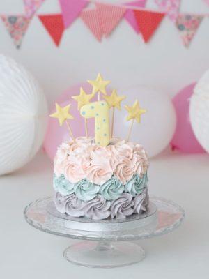 Delicada tarta de rosetones de crema en varios colores para sesión de fotos con bebé