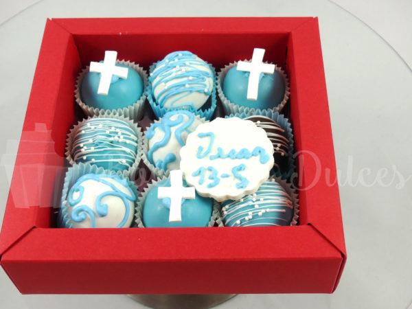 cajita con cake balls en blancos y azules y placa de choco