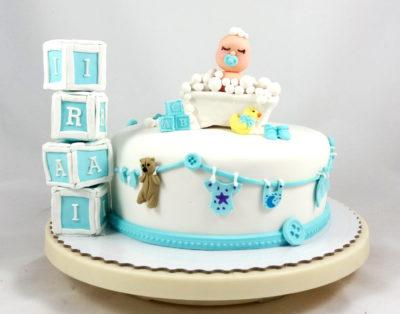 tarta con figura de bebé en bañera y nombre en cubos