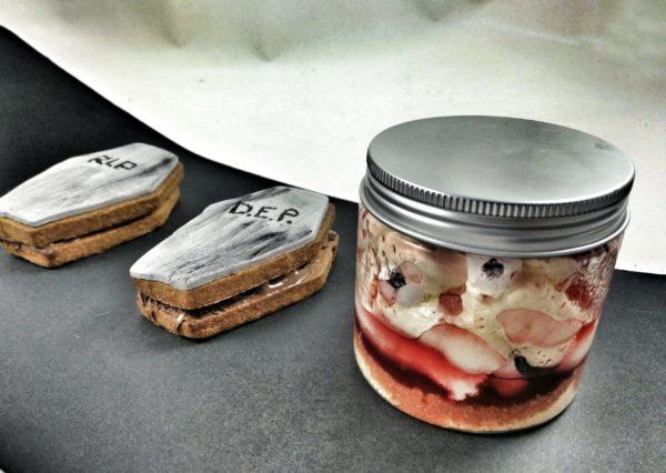 """tarro de pastel de queso con """"sangre"""" de mermelada de frambuesa y ojos de merengue y tumbras de sandwich de galleta y nutella"""