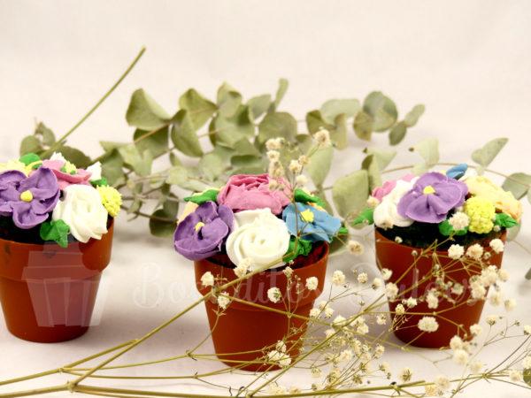 3 cupcakes con flores y maceta de chocolate